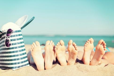 Füße liegen am Strand neben einer Badetasche