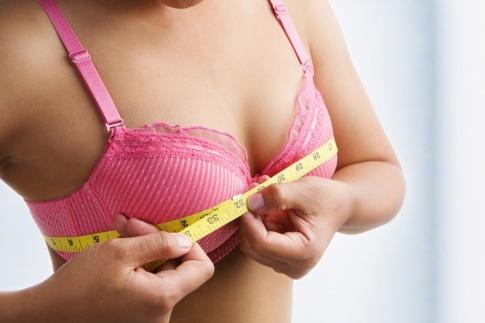 Eine Frau hält ein Maßband um die Brust