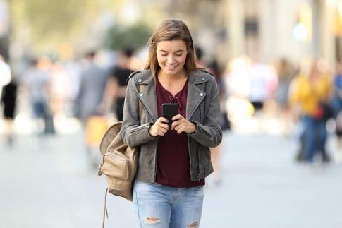 Eine junge Frau läuft in der Gegend herum und schaut dabei lächelnd auf ihr Smartphone.
