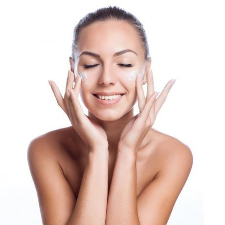 Eine Frau cremt ihr Gesicht ein und nimmt Kollagen Kosmetik Produkte