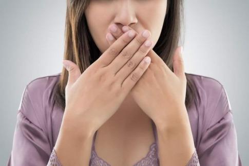 Eine Frau hält sich ihre Hände vor den Mund
