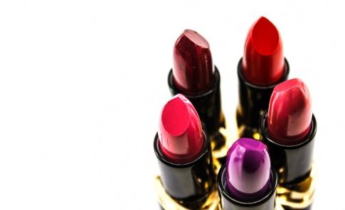 Auf dem Foto sind fünf verschiedene Lippenstifte in Rottönen abgebildet, die in einem Kreis aufgestellt sind