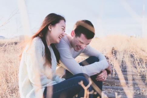 Eine Frau und ein Mann sitzen im hohen Gras auf Bahnschienen