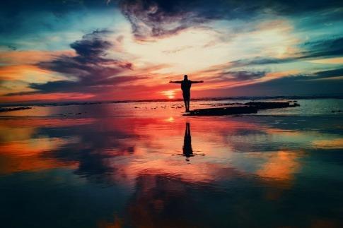 Ein Mensch steht im Sonnenuntergang am Meer und streckt seine Arme aus
