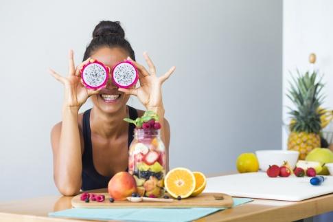 Eine Frau ist mit einem tropischen Fruchtsalat abgebildet und sie verdeckt sich die Augen mit einer Dragon Fruit.