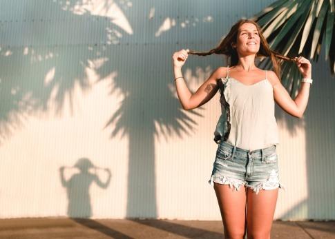 Eine fröhliche Frau reckt sich der Sonne entgegen, ihr Schatten ist in der Form eines jungen Mädchens mit Pferdeschwänzen.