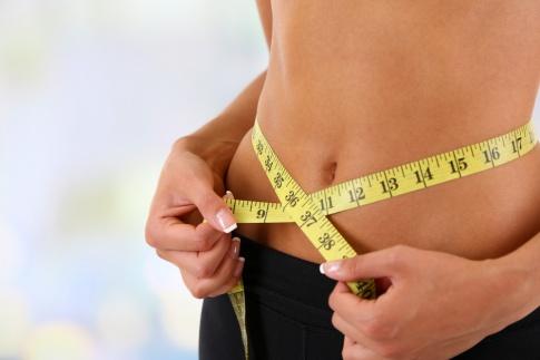 Frau mit Maßband um den Bauch