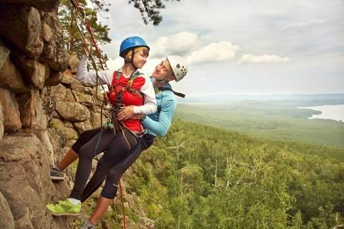Ein junges Paar hängt gesichert in einer Felswand.