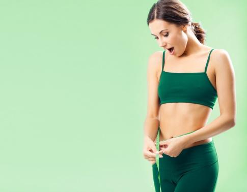 schlanker Bauch wird mit Maßband gemessen