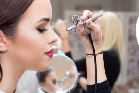 Eine Frau wird mit Airbrush geschminkt