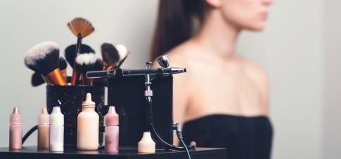 Schminkpinsel und das Airbrush-Equipment stehen vor einer Frau