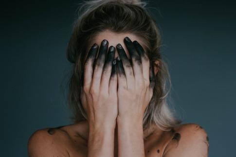 Eine Frau hält sich mit Aktivkohle auf den Händen das Gesicht zu