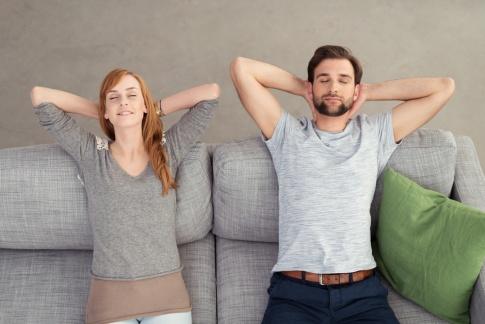Ein Mann und eine Frau liegen glücklich auf gepolsterten Möbeln, die die Akustik verbessern