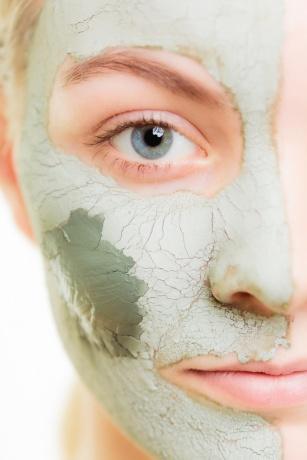 Die Frau hat die Hälfte ihres Gesichtes mit einer Algenmaske eingecremt