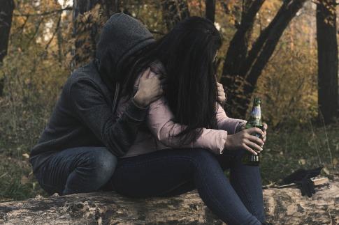 Zwei Personen halten eine Alkoholflasche in der Hand