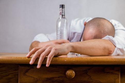 Ein Alkoholiker liegt am Tisch mit einer Flasche in der Hand