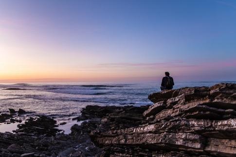 Ein Mann sitzt einsam und alleine auf Felsen am Meer