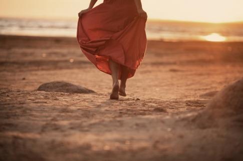 Eine Frau geht alleine am Strand