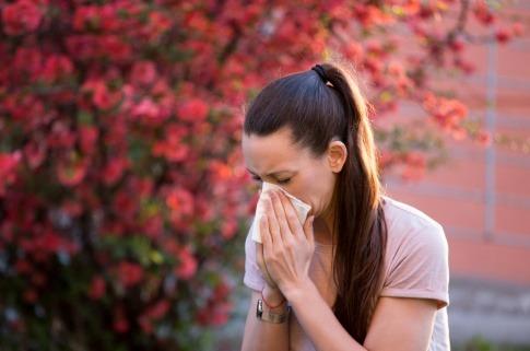 Frau niest vwegen Allergie vor blühendem Busch