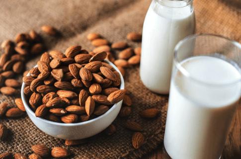 Nüsse liegen neben einem Glas Milch. Beide enthalten Aminosäuren