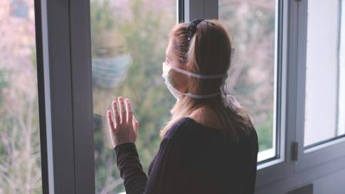 Eine Frau trägt einen weißen Mundschutz und schaut aus dem Fenster