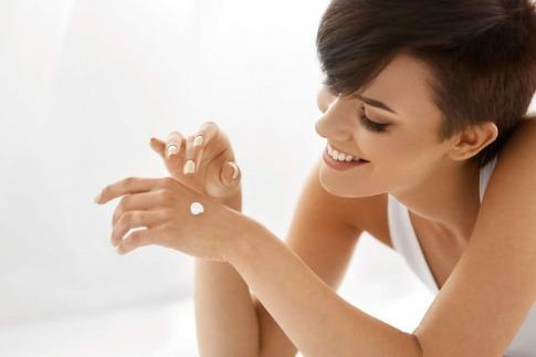 Frau die sich die Hände eincremt