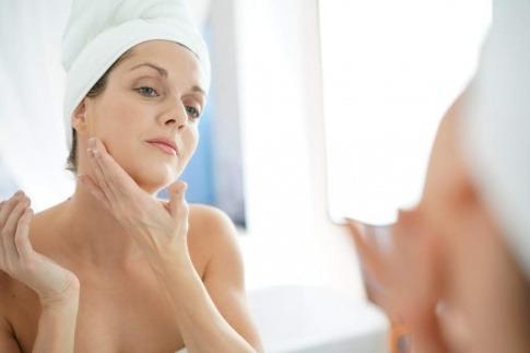Eine Frau gibt Anti-Aging Öl in ihr Gesicht