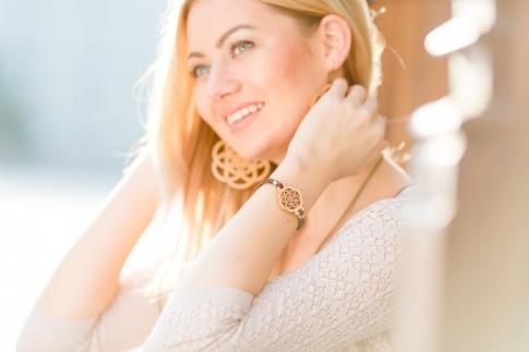Eine blonde Frau trägt ein Armband und Ohrringe aus Holz