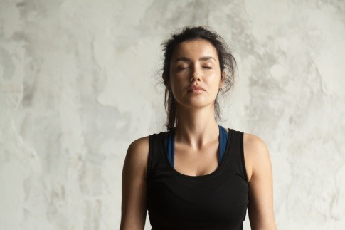 Eine Frau macht Atemübungen gegen Menstruationsschmerzen.