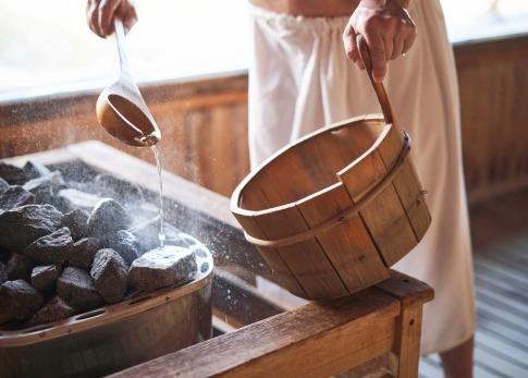Ein Mann macht einen Aufguss in der Sauna mit ätherischen Ölen
