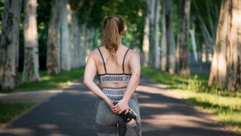 Eine Frau wärmt sich vor dem Joggen auf