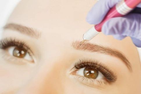 Frau bei einer Microblading Behandlung der Augenbrauen
