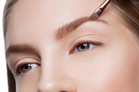 Die Augenbraue einer Frau wird natürlich geschminkt