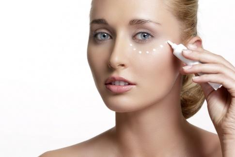 Eine Frau gibt sich eine koffeinhaltige Augencreme auf die Haut