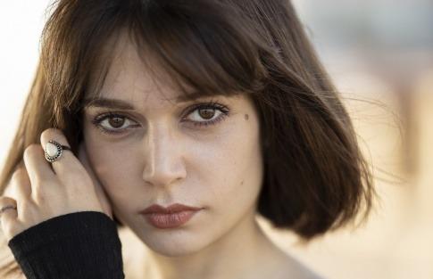 Eine Frau mit dunklen Haaren hat Augenringe