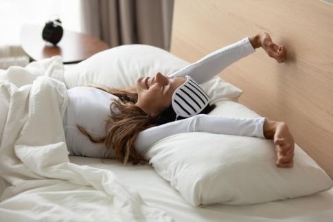 Eine Frau erwacht ausgeruht nach gutem Schlaf