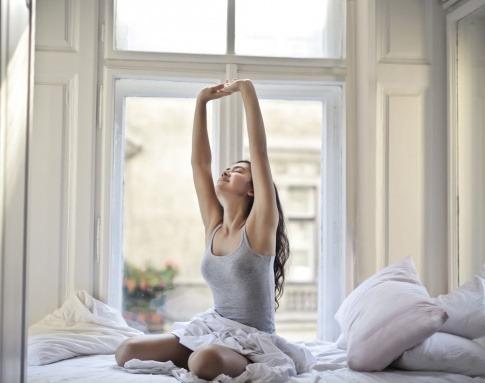 Eine Frau streckt sich ausgeruht am Bett