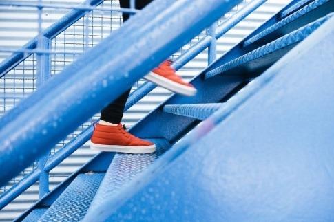 Ein Mensch mit orangefarbenen Schuhen geht eine Außentreppe aus Stahl nach oben