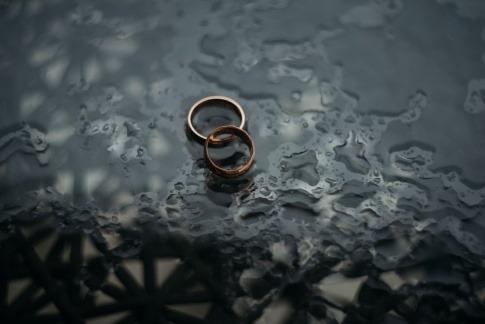 Zwei Eheringe im Regen als Zeichen für Auszeit von der Ehe