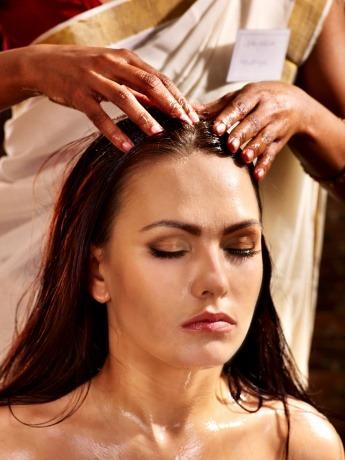 Eine Frau bekommt eine ayurvedische Kopfmassage
