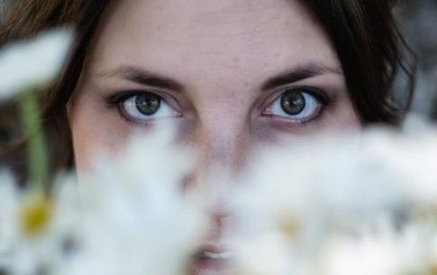 Eine Frau schaut hinter Kamille, aus der Azulen hergestellt wird, hervor