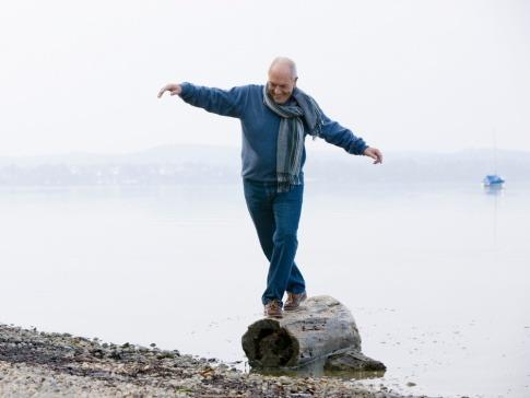 Ein älterer Mann balanciert auf einem Baumstamm