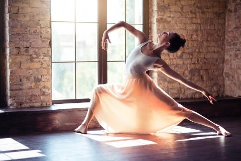 Eine Ballerina in Pose vor einem Fenster