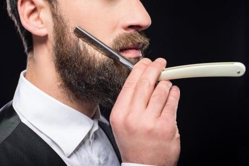 Ein Mann will sich seinen Bart richtig rasieren und stutzt seinen Vollbart dazu zunächst mit einer Bartschere.