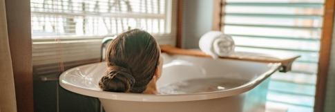 Eine Frau entspannt sich in der Badewanne, nachdem sie erfolgreich gelernt hat, wie man ein Basenbad selber machen kann.