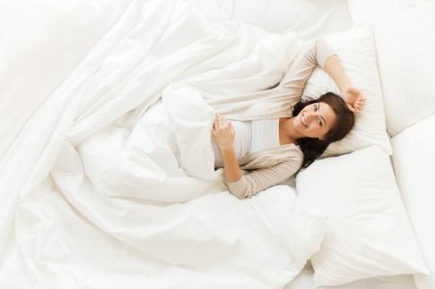 Eine Frau liegt zufrieden im Bett und kann besser schlafen in der Schwangerschaft