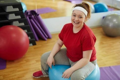 Eine Frau sitzt in einem Sportraum auf einem Gymnastikball und blickt zufrieden in die Kamera.