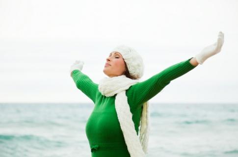 Eine Frau streckt ihre Arme auf die Seite und atmet bewusst