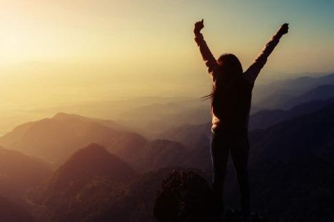 Eine Frau freut sich bewusst auf einem Berg