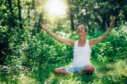 Frau meditiert bewusst im Wald